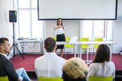 Business woman answering during educational team meeting or corporate training with woman speaker or coach. Woman answering during educational team meeting or stock photo