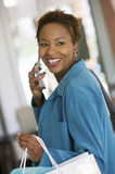 Woman Answering Mobilephone In Furniture Store Royalty Free Stock Photography