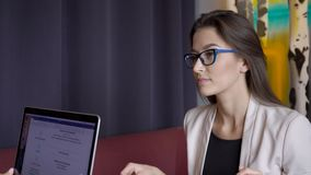 Woman answers questions that she is asked by person behind laptop. Portrait of young business lady with glasses, who listens attentively and gives explanations stock video footage