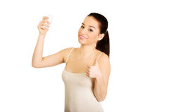 Woman with anti perspirant and thumbs up. Royalty Free Stock Photos