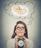 Woman anticipating a baby looking up holding alarm clock Stock Photography