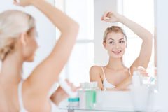 Woman with antiperspirant deodorant at bathroom Stock Photo