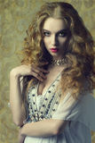 Woman with antique style. Lovely sensual woman wearing antique clothes and jewellery and posing with long curly hair. fashion vintage portrait Royalty Free Stock Photo