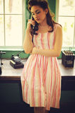 Woman with antique telephone. A woman in 50's dress and makeup using an antique telephone stock photo