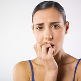WOMAN ANXIOUS. Portrait of a pretty young woman biting her fingers like she is stressed Royalty Free Stock Photos