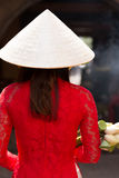 Woman in ao dai dress and conical hat. Rear view of young woman in ao dai dress and conical hat Royalty Free Stock Photos