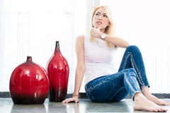Woman on apartment floor having idea Stock Image