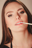 Woman aplying lip gloss Stock Photo
