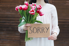Woman apologizing. Woman holding a card reading sorry Royalty Free Stock Photos