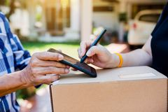 Woman appending signature sign on smartphone after accepting receive boxes from delivery man at home royalty free stock photography