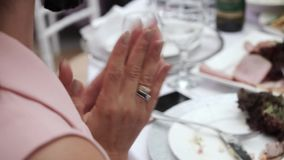 Woman applause at the party sitting at the table in restaurant