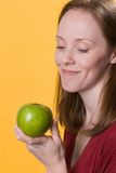Woman with apple-02. A smiling young woman looks longingly at a green apple she holds in her hand Stock Photos