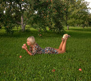 Woman and apple. Laying under apple tree Royalty Free Stock Photos