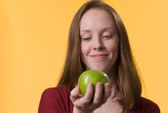 Woman with apple. A smiling young woman looks longingly at a green apple she holds in her hand Stock Images