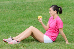 Woman with Apple. Young woman with sport wear eating and apple with green background Stock Images