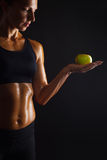 Woman with apple. Muscular woman with apple on dark background Stock Photography