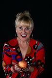 Woman with an apple. Attractive mature woman in colorful blouse holding an apple Royalty Free Stock Images