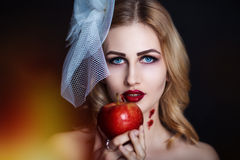 Woman with apple. Beautiful girl with creative make-up for the Halloween party. Bright colors eyes, red lips, stylish hair dress design. Conceptual art Snow Stock Images