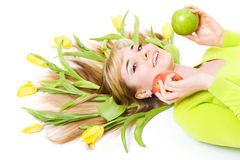 Woman with apple and bouquet of tulips in her hair Stock Photography