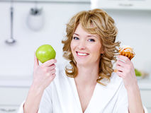 Woman with apple and cake in the kitchen Royalty Free Stock Photos