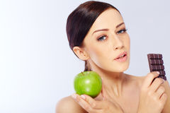 Woman with a apple and chocolate in her hand Stock Photo