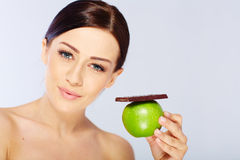 Woman with a apple and chocolate in her hand Royalty Free Stock Photography