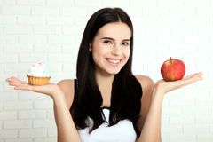 Woman with apple closeup face. Beautiful women exists to clean skin on the face that chooses to eat an apple or cake. Asian woman. Royalty Free Stock Images