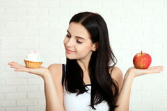 Woman with apple closeup face. Beautiful women exists to clean skin on the face that chooses to eat an apple or cake. Asian woman. Royalty Free Stock Image