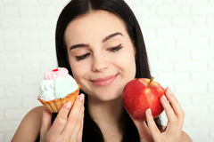 Woman with apple closeup face. Beautiful women exists to clean skin on the face that chooses to eat an apple or cake. Asian woman. Stock Photo