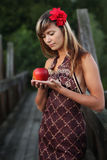 Woman with apple in the forest. Woman with red flower holding apple in the forest stock photo