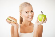 Woman with apple and hamburger Stock Photography
