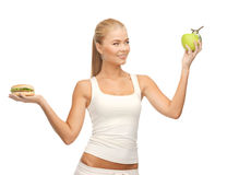 Woman with apple and hamburger Stock Photos
