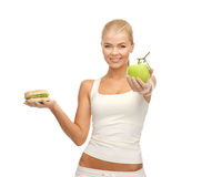Woman with apple and hamburger Royalty Free Stock Photo