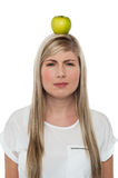 Woman with apple on her head Royalty Free Stock Photography