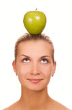 Woman an apple on her head. Beautiful woman with green juicy apple on her head Royalty Free Stock Photo