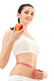 Woman with apple and measure tape Stock Images