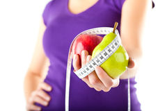 Woman with apple, pear and measuring tape Stock Photo