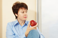 Woman with an apple sits next to the window Royalty Free Stock Photo