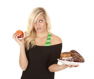 Woman with apple want donut Royalty Free Stock Photo