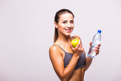 Woman with apple and water smiling with cheerful confidence isolated on white Royalty Free Stock Photography