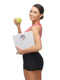 Woman with apple and weight scale. Picture of sporty woman with apple and weight scale Stock Image