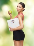 Woman with apple and weight scale. Picture of sporty woman with apple and weight scale Royalty Free Stock Photography