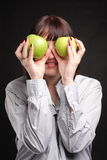Woman with apples. Green apples and young smiling woman in studio Royalty Free Stock Images