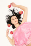 Woman and apples. Brunette in pink with flying apples on white background Royalty Free Stock Image