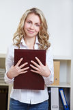Woman with application portfolio. Happy blonde woman standing with application portfolio in the office Royalty Free Stock Photo
