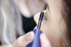 Woman applied eyeliner by makeup artist Royalty Free Stock Images
