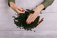 Woman applies coffee scrub on hands. With a red manicure Royalty Free Stock Photography