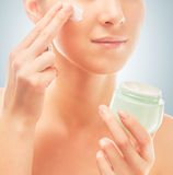 Woman applies cream on face, close-up Royalty Free Stock Photo