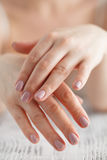 Woman applies cream on her hands after bath. Focus on hands Royalty Free Stock Images