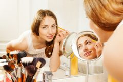 Woman applies eyebrow shadows with brush in bath. Portrait of beautiful young woman putting shadow powder on eyes with makeup brush in bathroom Stock Photo